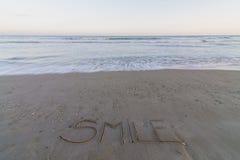 Smile. Word Smile written on the seashore stock image