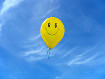 Smile yellow balloon over cloudy blue sky stock images