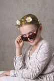 The Smile. Young girl with flowers in her yellow hair, posing for the camera with a pair of sunglasses Stock Image