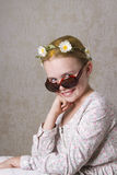 The Smile. Young girl with flowers in her yellow hair, posing for the camera with a pair of sunglasses Stock Photo