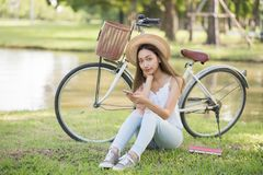 Smile young girl using mobile phone at the park. Portrait of Smile happy Asian woman with hat play social media from smartphone and sit near bicycle on grass Stock Photography