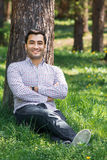 Smile young gorgeous man sitting on meadow Stock Images