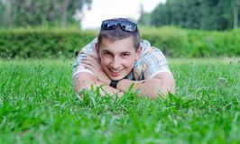 Smile of the young guy. The young guy smiles broadly lying on a green lawn Stock Image