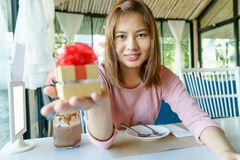 Smile young woman giving a golden present box with red ribbon to royalty free stock photos
