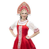 Smile young woman hands on hips portrait in russian traditional costume -- red sarafan and kokoshnik. Royalty Free Stock Images
