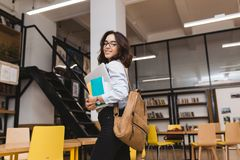 Smiled brunette young woman in black glasses walking with work stuff and laptop in library. Clever student, university. Life, smiling to camera, cheerful mood stock image