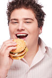 Smiled chubby and hamburger. Cute chubby eating a hamburger, isolated on white Royalty Free Stock Images