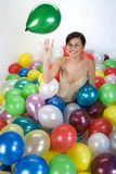 Smiled girl. In colorful baloons Stock Image