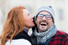 Smiled guy listen to woman. Very happy man from woman story. Woman whispers to man in glasses. Close up of man opened mouth. Royalty Free Stock Images