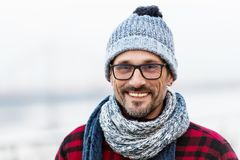 Smiled man in glasses. Portrait of smiling urban man in glasses and hat. Happy smiled guy in winter knitted hat and scarf. royalty free stock photos