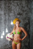 Smiled model in a bikini with bouquet of white flowers Royalty Free Stock Image