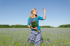 Smiled woman pose in cornflower bent with bouquet Royalty Free Stock Photo