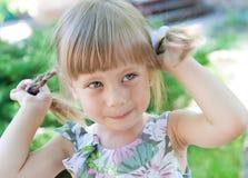 Smilegirl pequeno bonito com os pigtails ao ar livre. Imagem de Stock Royalty Free