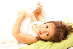 Smilegirl under the pillow. Little cute girl on her bed Royalty Free Stock Photo