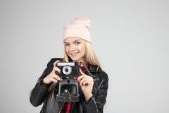 smileing与减速火箭的照片照相机的相当金发画象年轻少年行家妇女模型戴一个桃红色帽子 库存照片