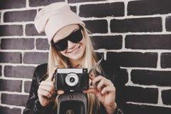 smileing与减速火箭的照片照相机的相当金发画象年轻少年行家妇女模型戴一个桃红色帽子 免版税图库摄影
