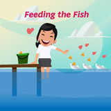 Smilely lady are feeding the fish -  Royalty Free Stock Photography
