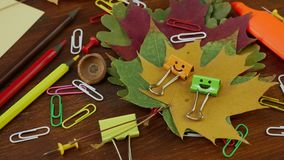 Smiles Binder Clips on Yellow Fallen Maple Leaves and School Office Supplies