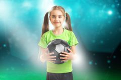 And smiles on cameralittle girl in green shirt holding a soccer. Cutie little girl in green shirt holding a soccer ball on stadium Stock Image