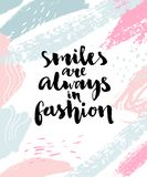 Smiles are always in fashion. Inspirational calligraphy quote on abstract brush strokes background Royalty Free Stock Photos