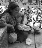Smiles. A Nepali woman feeds the pigeons in Durbar Square, Kathmandu, Nepal Royalty Free Stock Photo