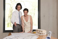 She smiles about the plans. Young man showing his wife the plans for their new home Royalty Free Stock Image