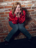 Smiles in a Red Shirt. Beautiful young redhead against a brick wall Stock Images
