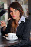 Smiles of young Asian businesswoman eating cake an Royalty Free Stock Photos