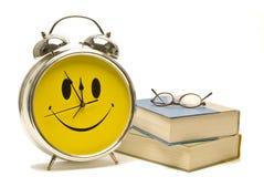 Smiley Alarm Clock With Books och läs- exponeringsglas Royaltyfri Foto