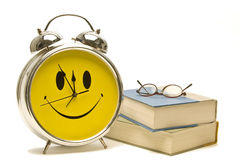 Smiley Alarm Clock With Books and Reading Glasses Royalty Free Stock Photo