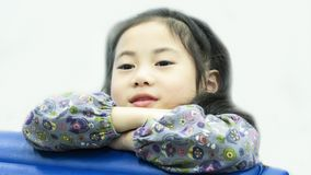 Smiley asian cute girl sitting daydreaming. The smiley asian cute girl sitting daydreaming in white background Royalty Free Stock Photo