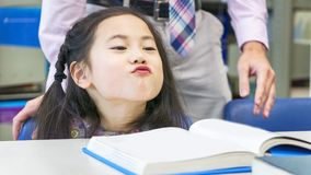 Smiley asian cute girl sitting and reading book on the table.  Royalty Free Stock Photography