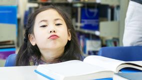 Smiley asian cute girl sitting and reading book on the table. The smiley asian cute girl sitting and reading book on the table Royalty Free Stock Images