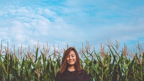 A smiley Asian woman closed her eyes and standing on front of corn field with blue sky stock photo