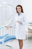 Smiley assistant shows the dentist's chair Stock Photography