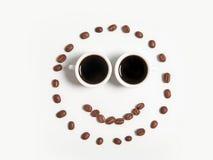 Smiley av kaffebönor i koppar som isoleras på vit Fotografering för Bildbyråer