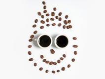 Smiley av kaffebönor i koppar som isoleras på vit Arkivfoton
