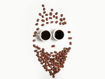 Smiley av kaffebönor i koppar som isoleras på vit Royaltyfri Foto