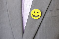 Smiley badge. A suited manager wearing a smiley bandge on grey suit Stock Photography