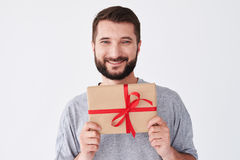 Smiley bearded man in grey t-shirt holding present box Royalty Free Stock Photos