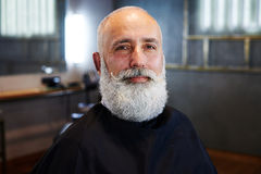 Smiley bearded senior man in barber shop Stock Photography