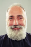 Smiley bearded senior man over light grey background Stock Photos