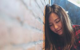 A smiley beautiful Asian woman closing her eyes while leaning on brick wall in modern cafe. Closeup image of a smiley beautiful Asian woman closing her eyes Royalty Free Stock Image