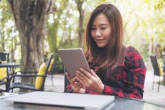 A smiley beautiful Asian woman holding ,using and looking at tablet pc with laptop on glass table sitting at outdoor Royalty Free Stock Photography