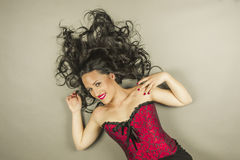 Smiley beautiful woman with long hair and red corset lay down Royalty Free Stock Images