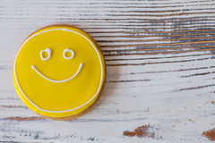 Smiley biscuit on wooden surface. Stock Image