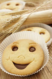 Smiley biscuits. Closeup of some smiley biscuits on a wooden worktop with some ears of wheat and a wooden rolling pin Stock Images