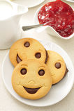 Smiley biscuits and jam. A plate with some smiley biscuits, a pot with milk and a bowl with jam on a set table Royalty Free Stock Images