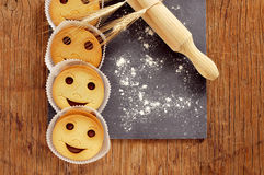 Smiley biscuits on a wooden rustic table. High-angle shot of some smiley biscuits, some ears of wheat, a wooden rolling pin, and wheat flour sprinkled in a black stock photo