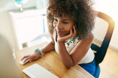 Smiley black woman using small business computer. Young pretty afro-american girl working on pc and smiling on blurred inside background Stock Photo